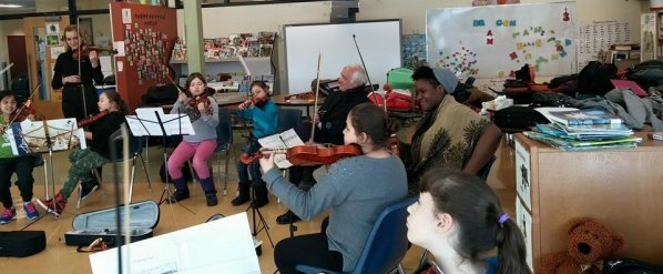 Musicians of the UNC Charlotte Chamber Orchestra collaborating with children at Kahnawake, Quebec. The gentleman in the center of the image is Ken Lambla, Dean of the College of Arts and Architecture at UNC Charlotte.